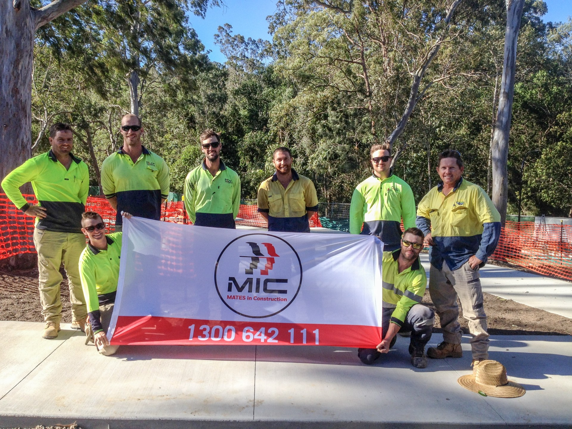 workers holding mates in construction banner